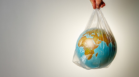 man's hand holds the earth in a plastic bag
