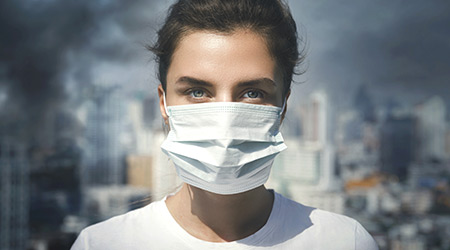 Air pollution in the city. Woman wearing face mask for protection