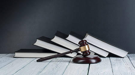 Open law book with a wooden judges gavel on table in a courtroom or law enforcement office on blue background