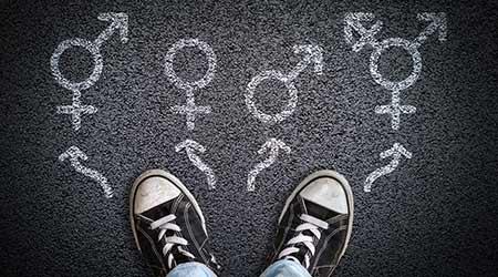 A person standing on asphalt road with gender symbols of male, female, bigender and transgender.