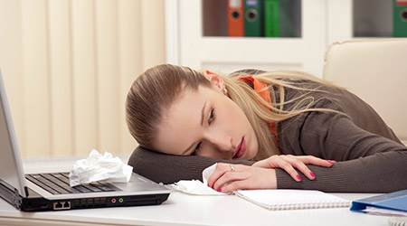 Portrait of a sick young lying on her desk in workplace