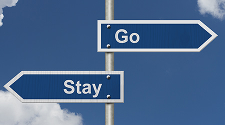 To Stay or to Go, Two Blue Road Sign with text Stay and Go with sky background