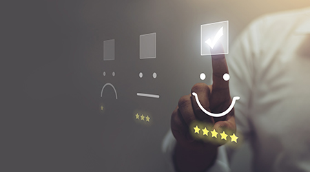 Businessman pressing smiley face emoticon on virtual touch screen
