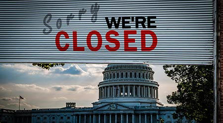 United States Capitol Building with a Old grunge weathered and dirty steel metal roller shutter door with Sorry we're closed text