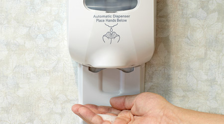 Picture of a person's hand using wall mounted automatic sanitizer dispenser