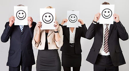 Group of unidentifiable business people holding happy faces