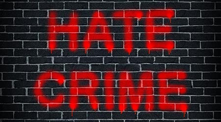 Hate crime social problem concept with a dark grey brick wall with graffiti spray painted as a symbol of racism and race discrimination as an illegal act of hatred and vandalism based on xenophobia
