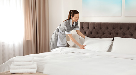 Young chambermaid making bed in hotel room