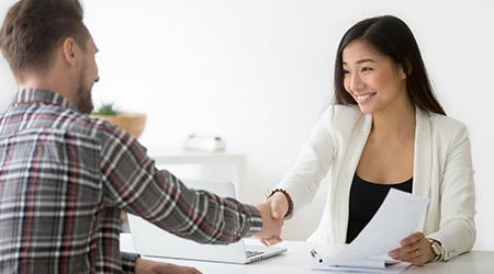 Smiling asian businesswoman handshaking businessman