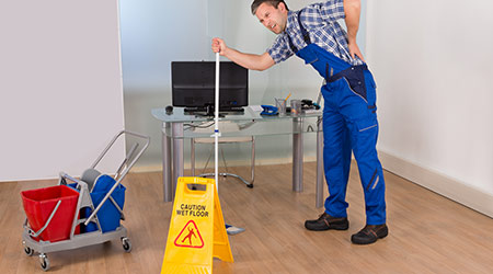 Male janitor suffering from back pain while working