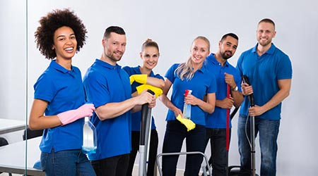 Happy Male And Female Janitors With Cleaning Equipment