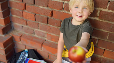 Student with big backpack and lunch bag shares his apple near the school building. School meals. Back to school