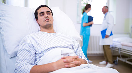 Sad man in a hospital gown