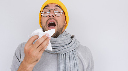 Portrait of sick handsome man wearing grey sweater, yellow hat and spectacles, blowing nose and sneeze into tissue
