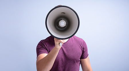 Close-up Of ManShouting Through A Megaphone Against Gray Background