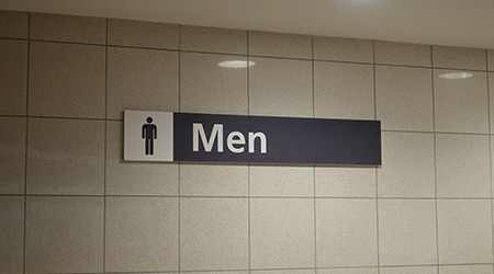 A sign signifying a men's bathroom or lavatory entrance