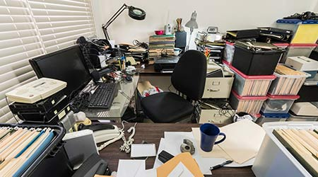 Messy business office with piles of files and disorganized clutter