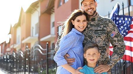 A military family outside of their home