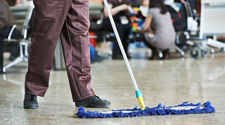 Janitor using a dust mop
