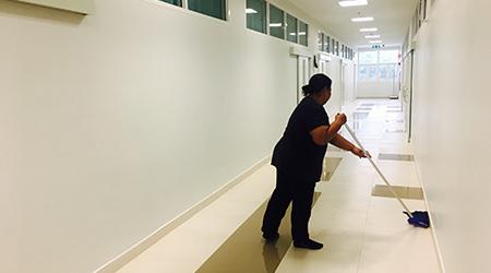 Female janitor mopping floor in hallway of new school building