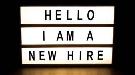 Light box sign proclaiming a new hire