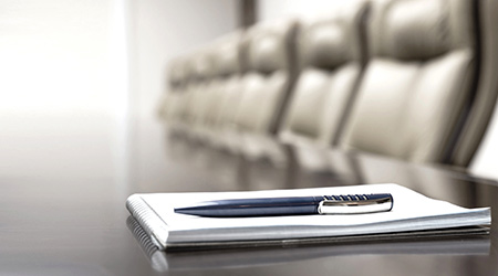 Pen and notepad on boardroom table