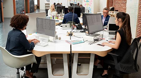 Business Team Working At Desks In Modern Open Plan Office