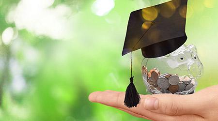 Hand holding clear piggy bank wearing a graduation cap