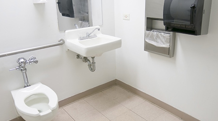 Clean public hospital bathroom with handrail soap and paper towel dispenser