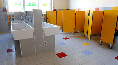 inside the bathroom of the nursery school with white sinks and doors yellow