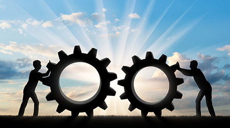 Silhouette of two people who want to connect the two gears in a single mechanism