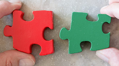 Business puzzle strategy. Two jigsaw pieces as metaphor for strong partnership, teamwork and success