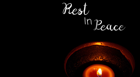 "Yellow light candle in modern cup and word ""Rest in Peace"" isolated on black background. End of life. Sadness. Free space for any text design."
