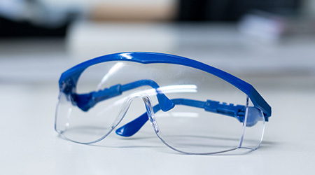 Close-up of blue safety goggles on a desk in a research lab.