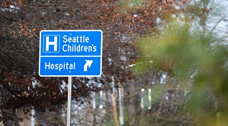 Street sign pointing to Seattle Children's Hospital, with space for text on the right
