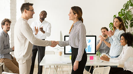 Smiling female boss promoting worker rewarding handshaking motivated worker showing respect