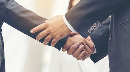 Two guys in suits shaking hands