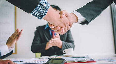 Business people shake hands after agreeing to join a business