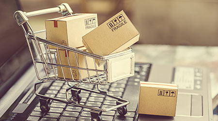 Paper boxes in a shopping cart on a laptop keyboard