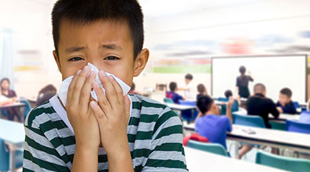Kid at school blowing his nose with a tissue