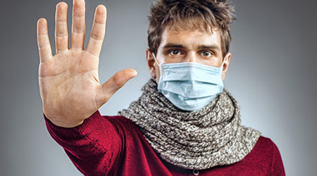 Stop the infection! Young man wears protective mask and showing gesture stop