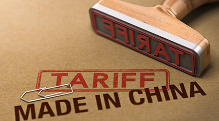 rubber stamp over cardboard background with the words made in China and tariff