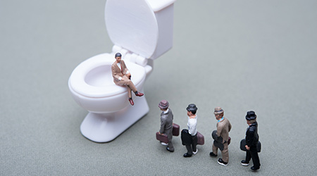 Businessmen lined up in the toilet