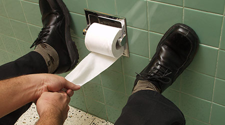 Hands pulling at toilet paper