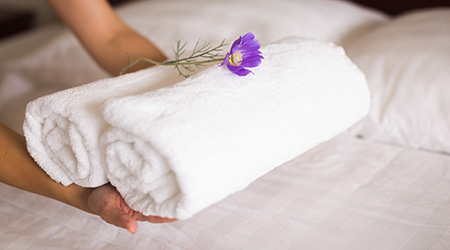white hotel bed sheets and towel set. maid cleaning bed