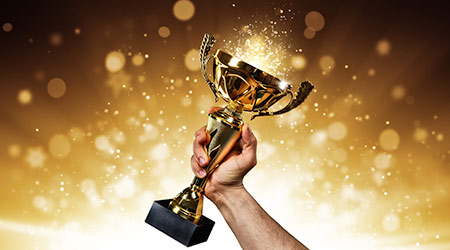 Man holding up a gold trophy cup with abstract shiny background