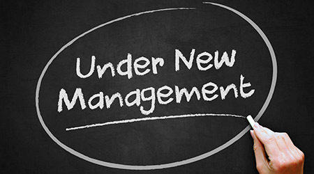 A hand writing 'Under New Management' on chalkboard