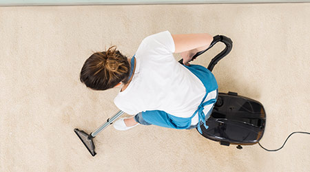 Young Female Janitor In Uniform Vacuuming Floor