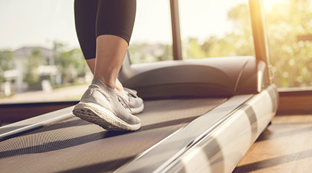 Woman running in machine treadmill at fitness gym at morning