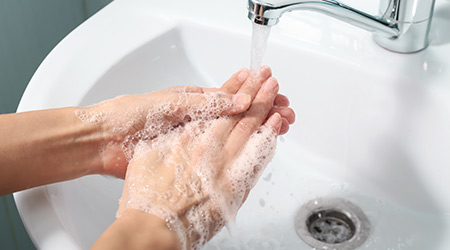 Woman washing hands in sink